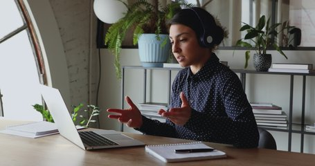 Young indian business woman wearing headphones communicating by video call. Ethnic businesswoman speaking looking at laptop computer, online conference distance office chat, virtual training concept.