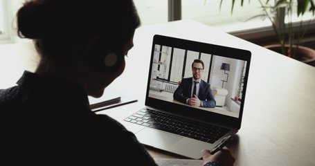 Over shoulder close up view of business woman conferencing with male executive in distance video chat on computer screen. Online corporate webcam meeting, virtual training, remote work communication.