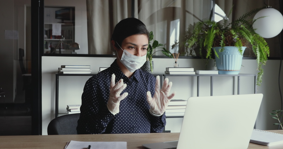 Young indian business woman wearing medical gloves and face mask communicating by video call on laptop computer. Online conference distance remote home office during coronavirus covid 19 quarantine. Royalty-Free Stock Footage #1049817001