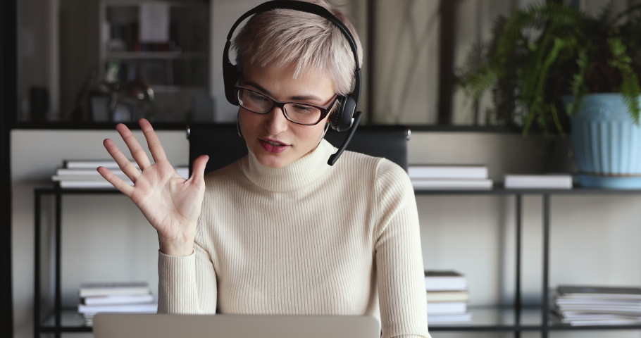 Confident female office worker wears headset conference video calling looking at laptop computer. Young businesswoman customer service manager speaking to webcam communicating in distance remote chat. Royalty-Free Stock Footage #1049817007