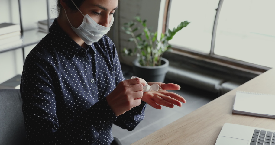 Young indian business woman wearing face mask cleaning hands with sanitizer gel at workplace. Female worker using alcohol sanitiser working from home office on computer to prevent coronavirus concept. Royalty-Free Stock Footage #1049817028