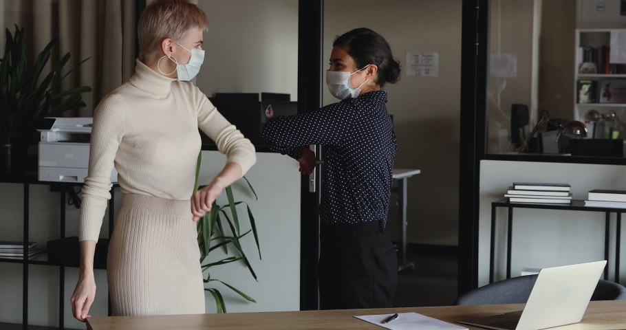 Indian and caucasian businesswomen wear medical face masks greeting with elbow bump work together in office. Two female colleagues avoid touch for coronavirus protection covid 19 spreading prevention.