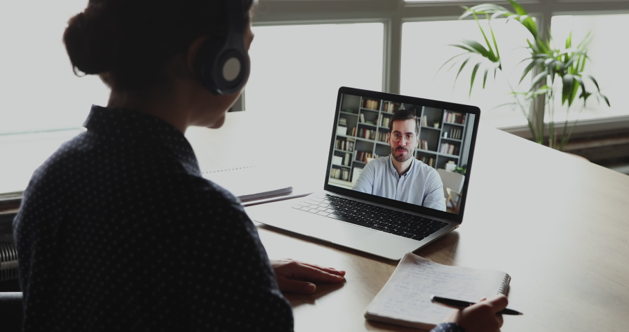 Indian female student makes conference video call on laptop computer talks with web tutor, online teacher in remote webcam chat on screen. Distance education class concept. Over shoulder close up view Royalty-Free Stock Footage #1049817121