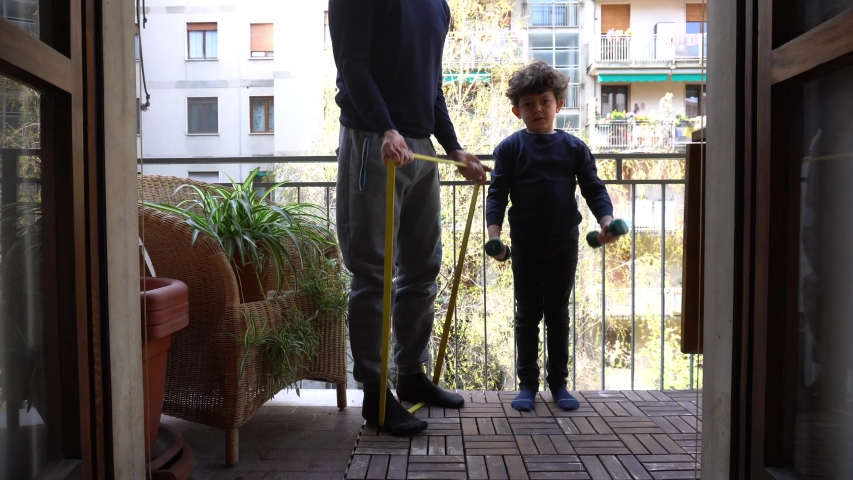 Europe, Italy , Milan - children boy  five years with mask and father at home during quarantine due n-cov19 Coronavirus outbreak - life stile in apartment, do gymnastics and weights on the balcony | Shutterstock HD Video #1049822899