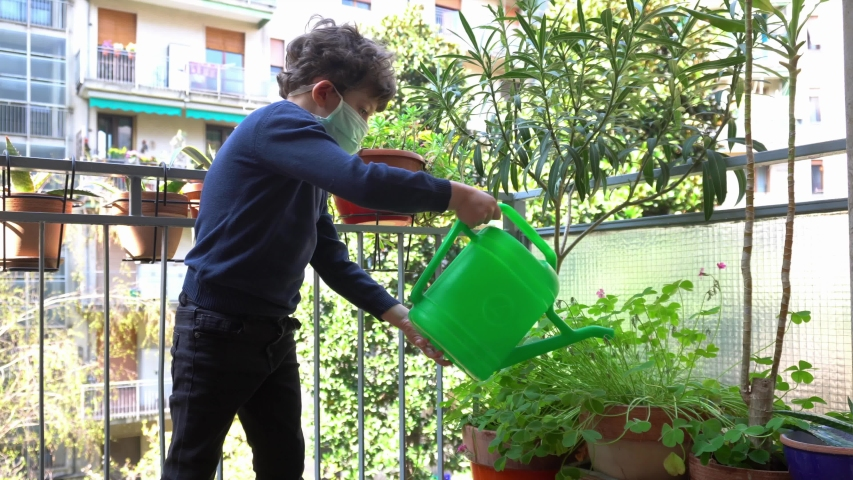 Europe, Italy , Milan - children boy  five yewith mask ars at home during quarantine due n-cov19 Coronavirus outbreak - life stile in apartment - water the plant and flowers on the balcony Royalty-Free Stock Footage #1049823034