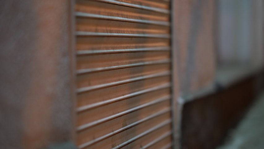 Roller shutters at closed shop door on a city street in the evening, urban streets at night.   Shutterstock HD Video #1049825161