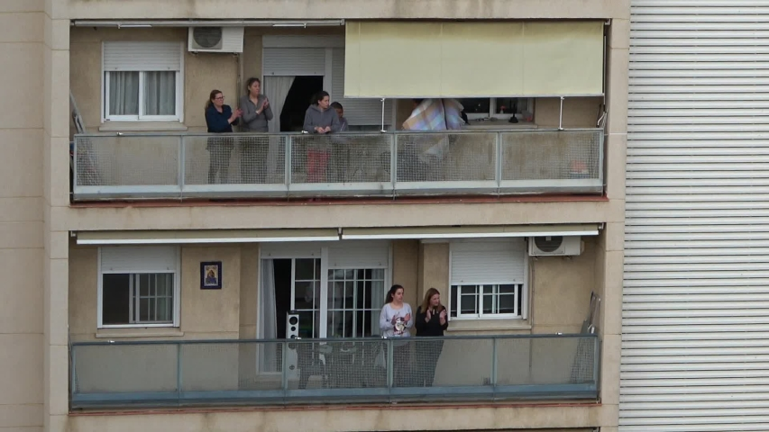 Huelva, Spain - April 5, 2020: Citizens staying at home and clapping everyday on balconies at 8 PM during the epidemic period of deadly coronavirus. People in quarantine in Spain