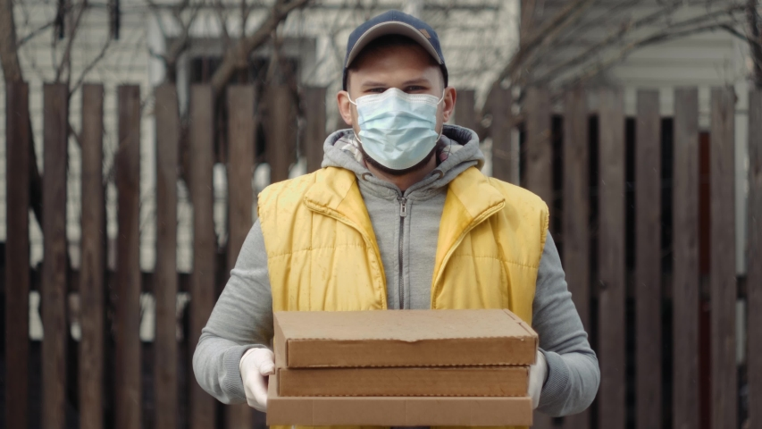 Delivery man holding cardboard boxes in medical rubber gloves and mask coronavirus pandemic quarantine home isolation. Fast and free pizza supermarket Delivery. Online shopping and Express e-commerce. | Shutterstock HD Video #1049836153