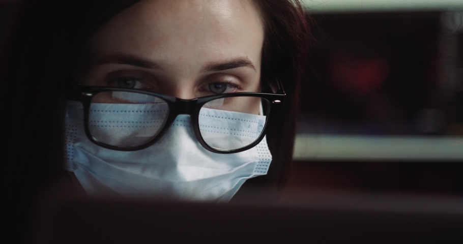 Coronavirus quarantine. Woman at the office with mask, self home isolation. Business women wear masks to protect and take care of their health. Home working with computer. Working from home. Royalty-Free Stock Footage #1049836156