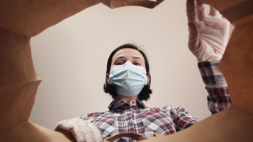 Young woman carefully opens box delivery from online store. Coronavirus pandemic quarantine, girl portrait with personal protective equipment gloves and a medical mask on face, second wave covid