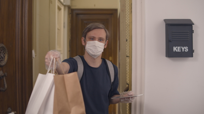 Postman or delivery man carry small box deliver to customer at home. Man wearing mask prevent covid or coranavirus quarantine pandemic. Social distancing home isolation work concept. | Shutterstock HD Video #1049836186