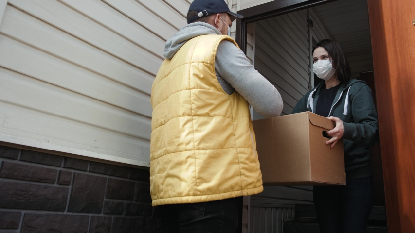 Postman or delivery man carry small box deliver to young woman customer at home. Man wearing mask prevent covid or coranavirus quarantine pandemic. Social distancing home isolation work concept. | Shutterstock HD Video #1049836198
