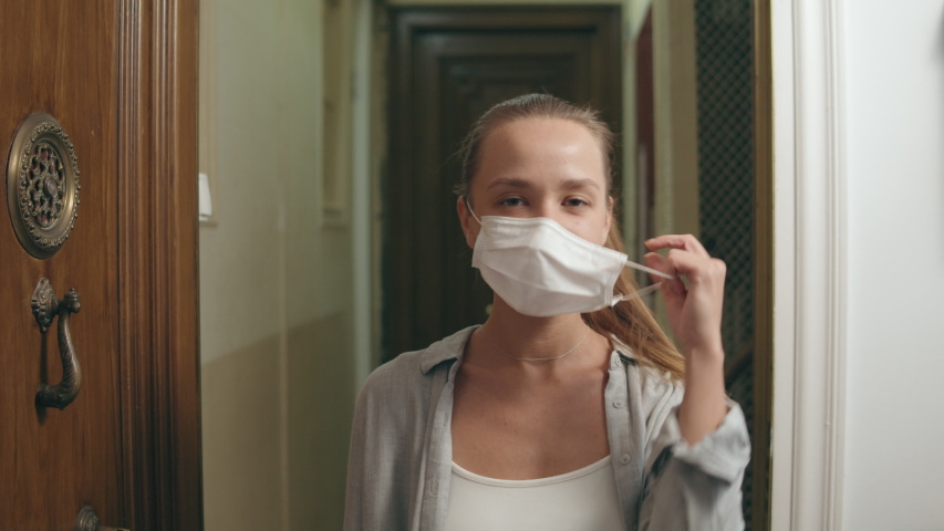 Happy positive girl, young beautiful woman takes off protective medical mask from face, smiling. Happy end quarantine and home isolation. Victory over coronavirus. Pandemic Covid-19. | Shutterstock HD Video #1049836216