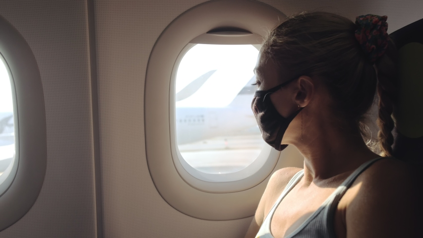 Woman travel caucasian at plane with wearing protective medical mask. Girl tourist at aircraft with protect respirator. Concept virus protection coronavirus epidemic sars-cov-2 covid-19 2019-ncov. | Shutterstock HD Video #1049839891
