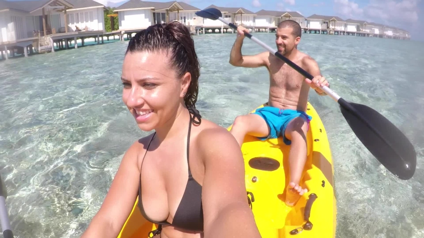 Couple on a kayak at Maldives seaside resort - Young happy couple enjoying summer vacation and having fun in a canoe on the water - Summer and sport concepts