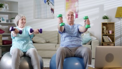 Joyous senior couple sitting on exercise balls, watching online workout on laptop and doing dumbbell wrist twist while training together at home