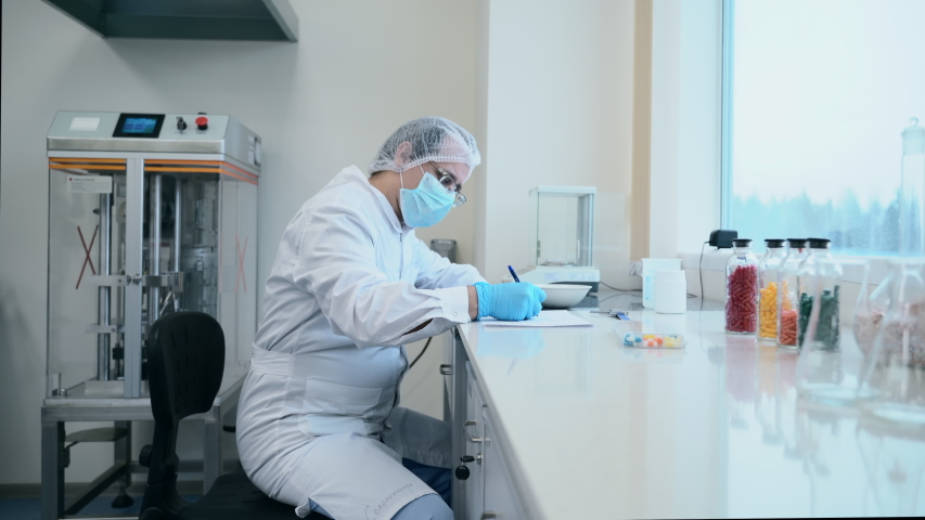 Doctor scientist sitting in pharmaceutical laboratory doing measurement of tablet. spbas testing, inspecting pills before sale. concept coronavirus spread epidemic cure | Shutterstock HD Video #1049856004