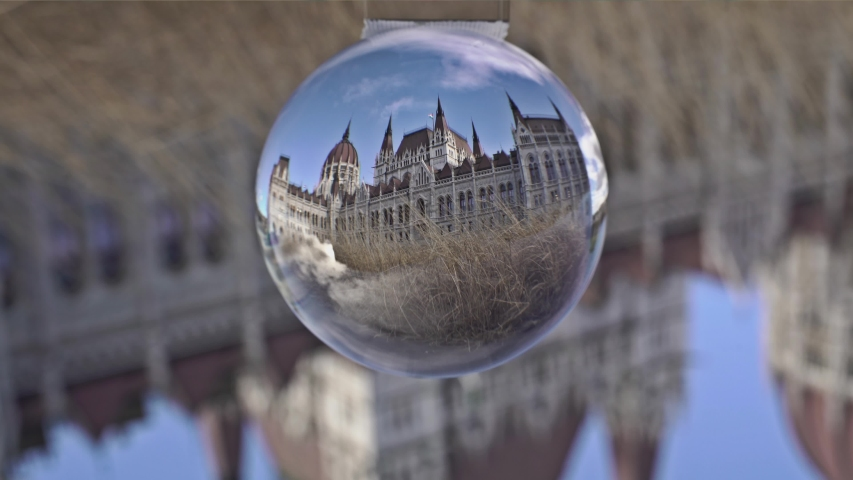 Hungarian Parliament at daytime in Budapest. One of the most beautiful buildings in the Hungarian capital in crystal glass ball stock photo.  | Shutterstock HD Video #1049858551