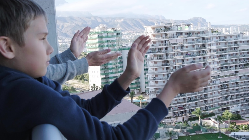Family applauding medical staff from their balcony. People in Spain every evening clapping on balconies and windows in support of health workers during the Coronavirus pandemic | Shutterstock HD Video #1049861359