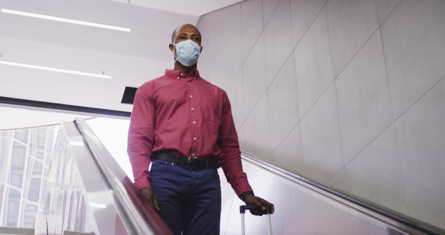African American man wearing a face masks against air pollution and covid19 coronavirus, using an escalator in a metro station and holding a suitcase. | Shutterstock HD Video #1049865640