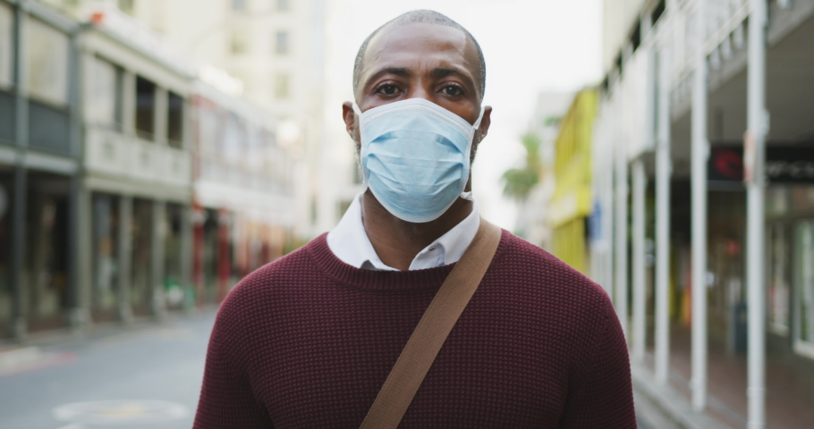 Portrait of an African American man out and about in the city streets during the day, wearing a face mask against air pollution and covid19 coronavirus. | Shutterstock HD Video #1049867416