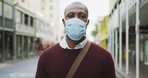 Portrait of an African American man out and about in the city streets during the day, wearing a face mask against air pollution and covid19 coronavirus.