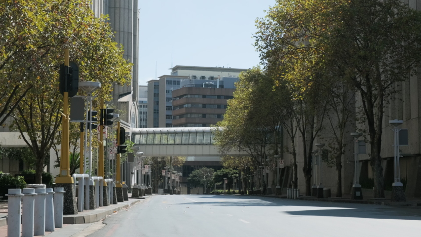 A wide shot of a quiet, empty street in Johannesburg city centre during the covid-19 coronavirus lockdown.  | Shutterstock HD Video #1049868244