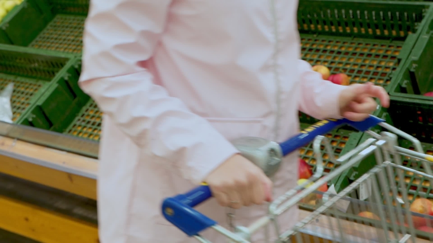 Woman with a grocery cart drives past empty fruit shelves | Shutterstock HD Video #1049876869