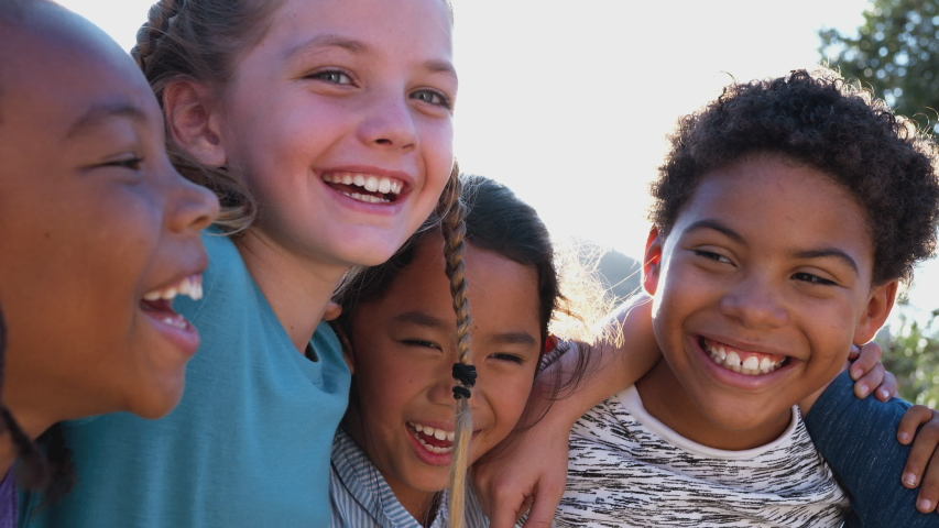 Camera tracks along faces of group of children hanging out with friends outdoors with arms around each other against flaring sun - shot in slow motion Royalty-Free Stock Footage #1049877082