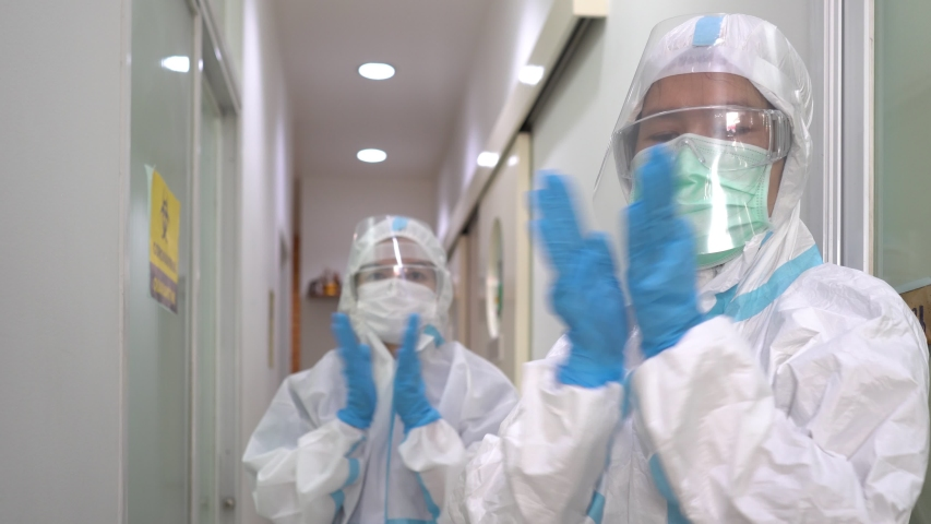 Two doctors in personal protective equipments clapping their hands to cerebrate the success of treatment. covid-19, coronavirus, medical, gratitude, healthcare concept