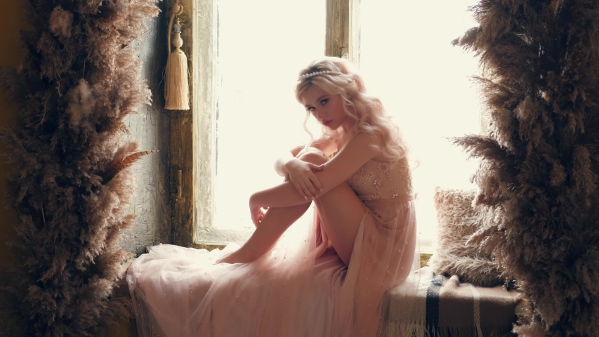Beauty young sexy sad woman princess sitting on window. fairy tale girl. medieval castle interior old room reed decor. Hairstyle blonde curly hair. Pearl vintage diadem. Beige vintage dress.