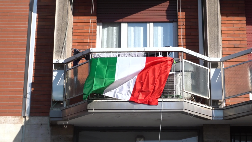 EUROPE, ITALY , MILAN  - Life in downtown during n-cov19 Coronavirus outbreak -  Flag of Italy hanging on the balcony of a house  Royalty-Free Stock Footage #1049896456
