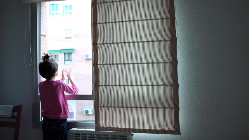 Girl in Spain clapping in the window in support of people who fight against the coronavirus