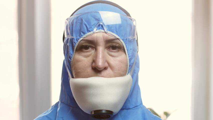 Portrait of a caucasian female epidemiologist protecting patients from masked coronavirus COVID-19. The global pandemic epidemic, Europe, Italy, USA. Dr. virologist is preparing to save people | Shutterstock HD Video #1049911423