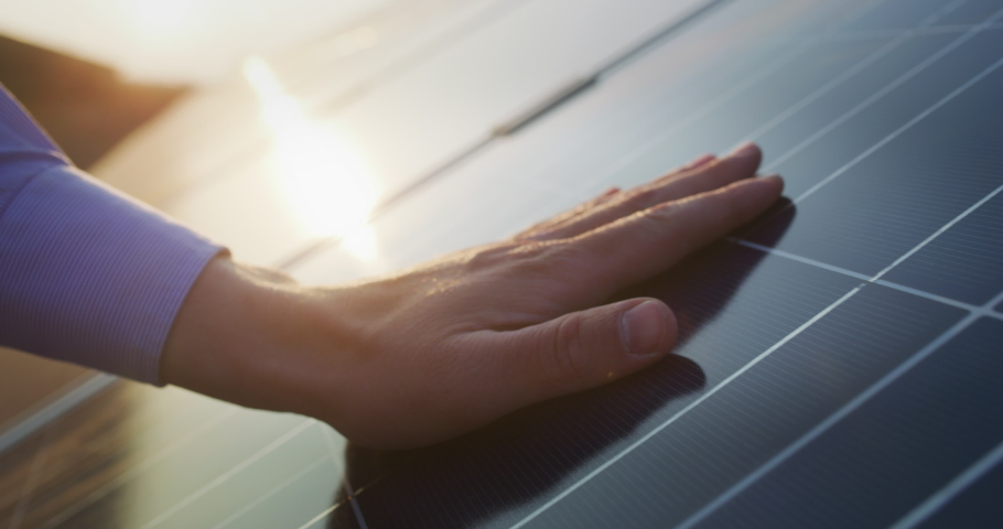 Close up of a young engineer hand is checking the operation of sun and cleanliness of photovoltaic solar panels on a sunset. Concept.renewable energy, technology, electricity, service, green, future.