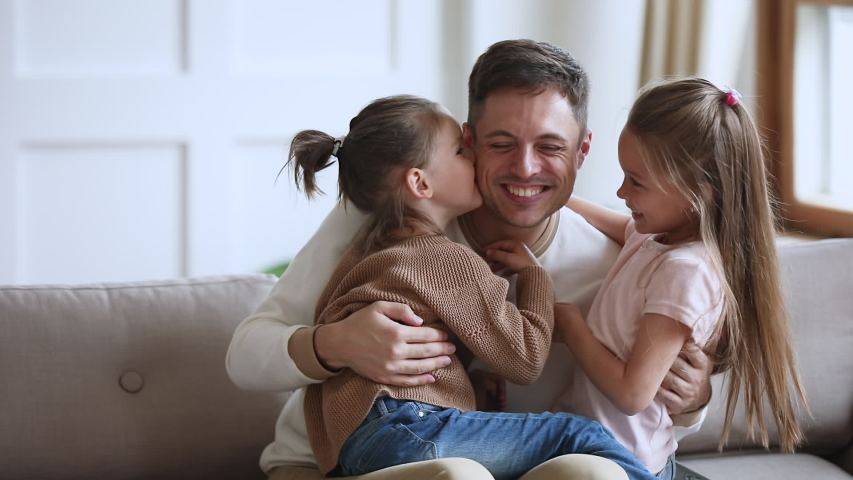 Happy young handsome father sitting on sofa, holding on lap small children daughters, enjoying tender sweet moment at home. Cute little kids girls embracing kissing smiling father, slow motion.
