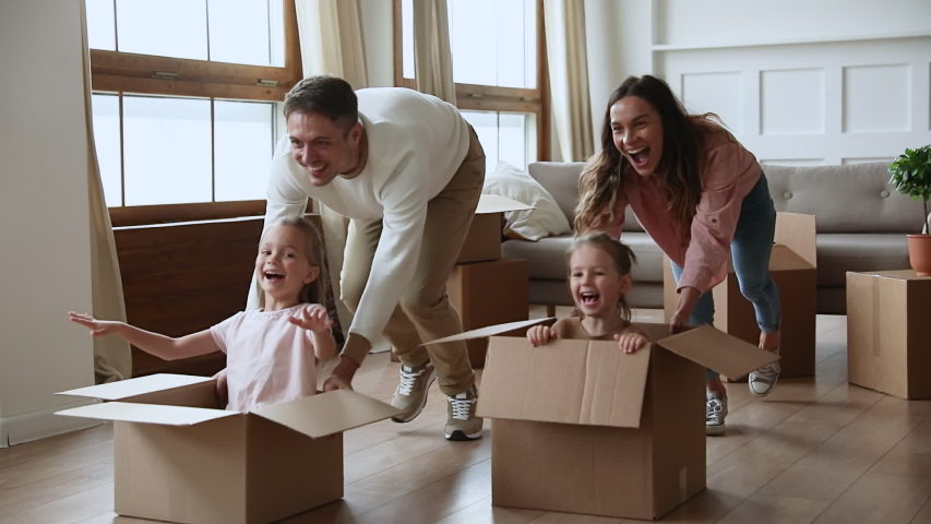 Slow motion active carefree young couple parents pushing huge cardboard boxes with kids, running forward, slow motion. Happy father and mother playing, having fun with adorable children daughters.