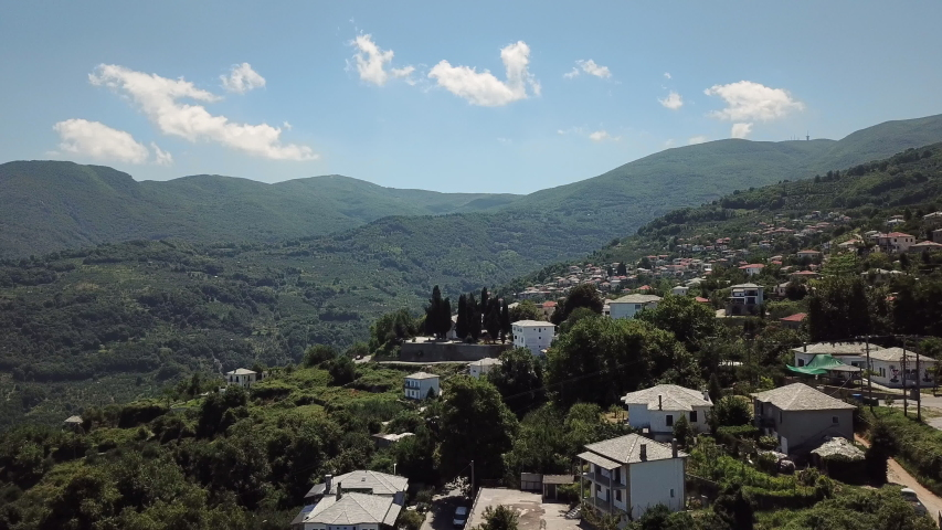 4K aerial footage of a drone flying above Zagora village in Pelion, Greece. The lush green mountain is visible beyond the traditional village. | Shutterstock HD Video #1049916454