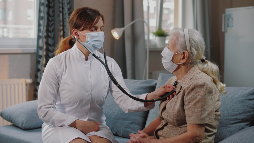 Female doctor use stethoscope to listen heart of elderly woman patient. Nurse home visit, checking health of old senior woman during coronavirus, covid-19 quarantine. | Shutterstock HD Video #1049916637