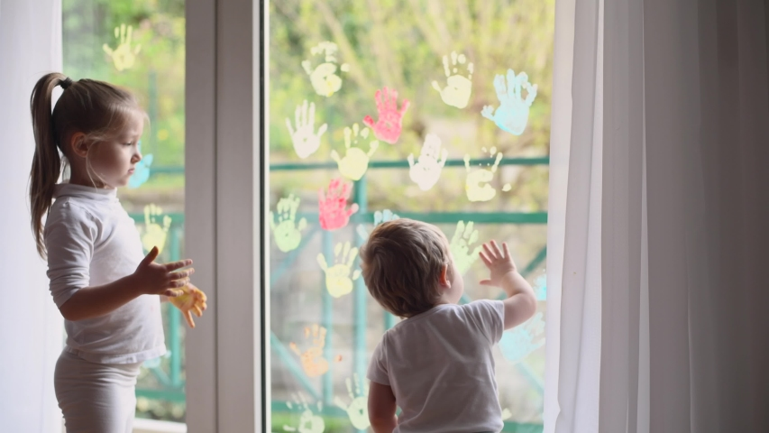 Children paint with palms on the window. Quarantine Stay at home | Shutterstock HD Video #1049920105