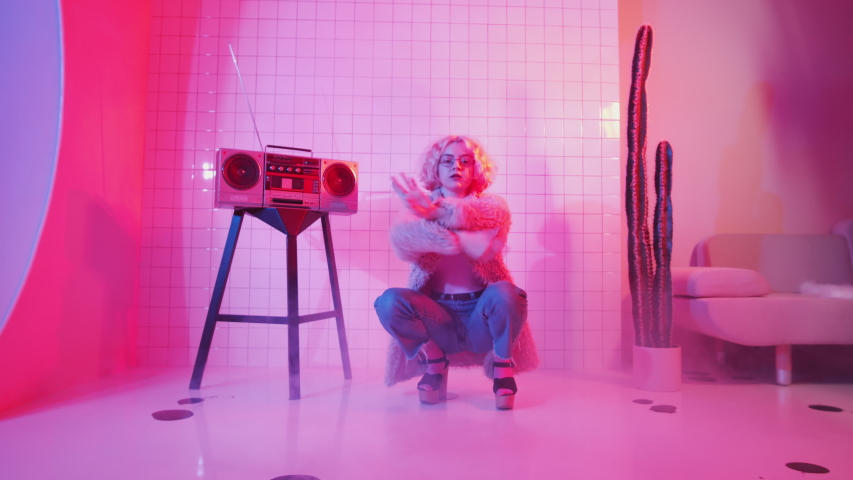 Young blonde female dancer in glamorous outfit showing vogue hands performance and looking at camera while sitting in squat near retro cassette player in studio with pink neon light | Shutterstock HD Video #1049922793