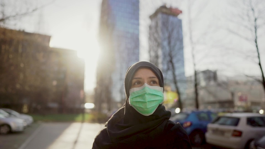 Female Muslim with protective surgical mask.Hijab woman wearing mask in the city.Coronavirus COVID-19 pandemic lifestyle in Islamic country culture.Spiritual praying concerned person.Faith challenge | Shutterstock HD Video #1049923012