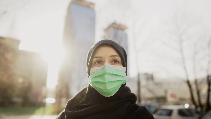 Female Muslim with protective surgical mask.Hijab woman wearing mask in the city.Coronavirus COVID-19 pandemic lifestyle in Islamic country culture.Spiritual praying concerned person.Faith challenge Royalty-Free Stock Footage #1049923015