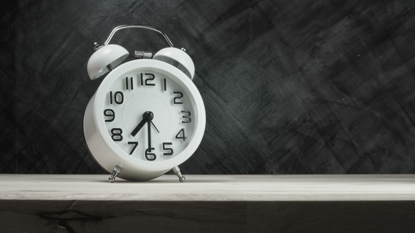 Time lapse of a white vintage alarm clock on wood table with the dark background, time start 07.30 run fast to 07.45  | Shutterstock HD Video #1049924320