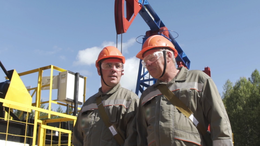 Two man oil workers in orange helmets walking and talking near oil pump jacks. Engineers overseeing site of crude oil production. Balancing drive rod pumps oil rocker. Slow motion | Shutterstock HD Video #1049936203