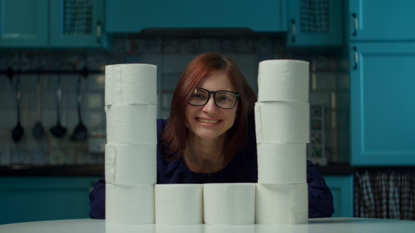 Young 30s woman in glasses making toilet paper rolls tower sitting at home on kitchen during coronavirus COVID-19 quarantine. Funny concept of toilet paper deficit.  | Shutterstock HD Video #1049939242