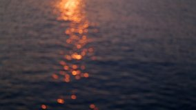 Beautiful defocused abstract golden blurry sea water background. Aerial view at soft waves of sea with soft sunset sun light reflection on peaceful surface.