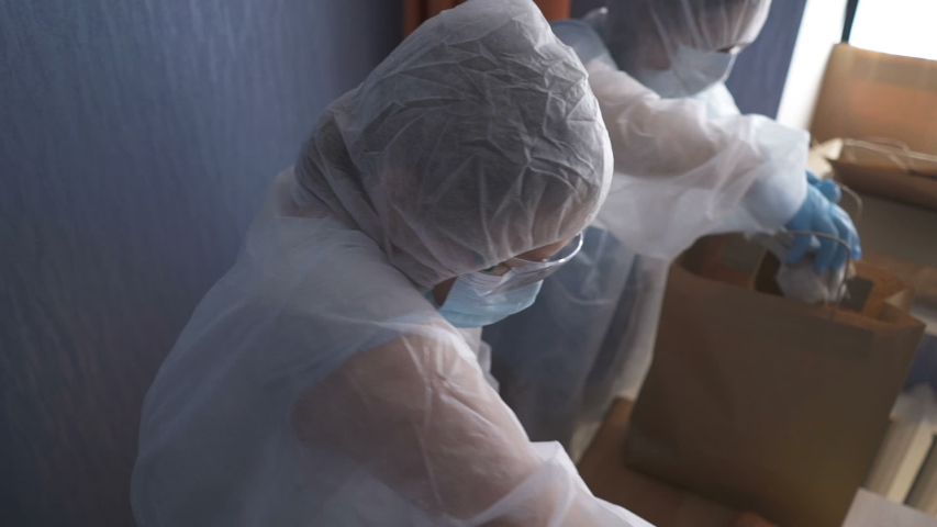 Volunteers in protective suits pack products. Food delivery services during coronavirus pandemic for working from home and social distancing. Shopping online. Royalty-Free Stock Footage #1049953696