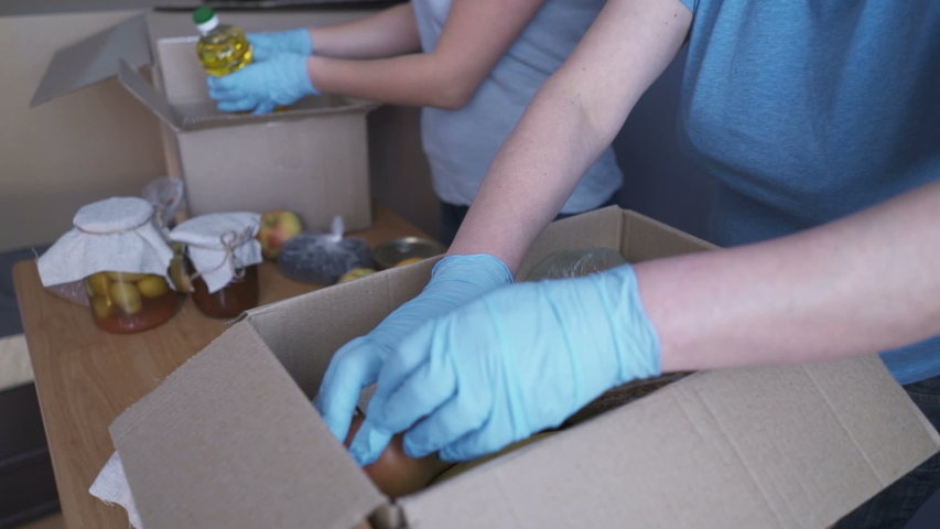 Volunteers in protective suits pack products. Food delivery services during coronavirus pandemic for working from home and social distancing. Shopping online. | Shutterstock HD Video #1049953699