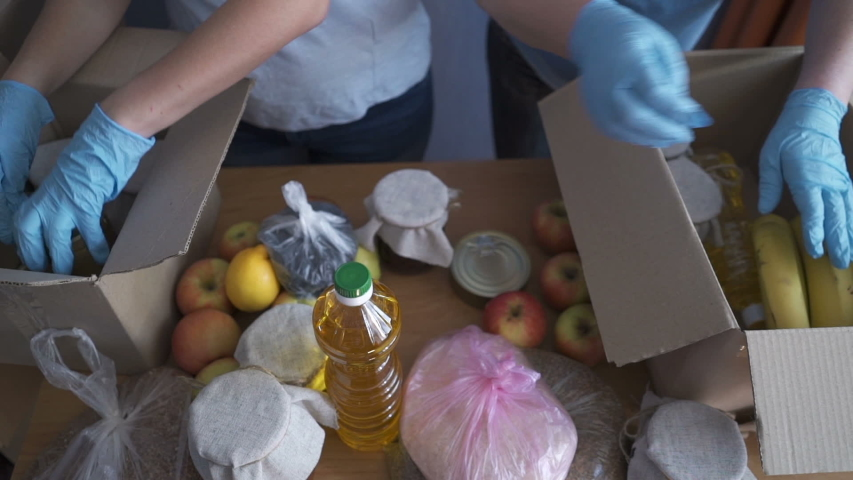 Volunteers in protective suits pack products. Food delivery services during coronavirus pandemic for working from home and social distancing. Shopping online.
